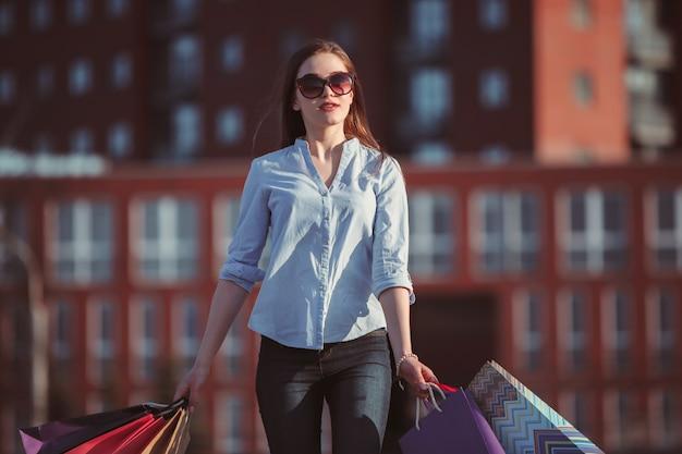 Das mädchen, das mit einkaufstüten auf stadtstraßen am sonnigen tag geht