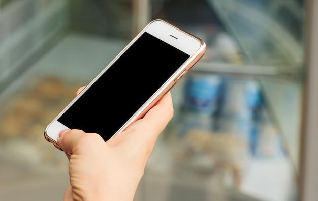 Das mädchen, das smartphone, straßenlaterne hält, ist ein tag, unscharfer hintergrund