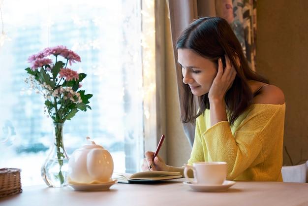 Das mädchen der jungen frau, das an einem tisch nahe dem fenster sitzt, das tee und glücklichen unbeschwerten freudigen ausdruck trinkt, macht notizen in einem notizbuch und macht pläne für jeden tag.