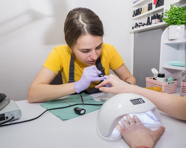 Das mädchen, der meister, lackiert die nägel des kunden im salon. nagelpflegekonzept