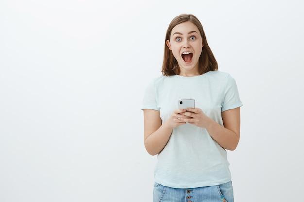 Das mädchen erhielt eine einladung zu einer großartigen party über nachrichten im internet, in denen das smartphone erstaunt und erfreut über den vor aufregung geöffneten mund blickte, der glücklich über die graue wand blickte