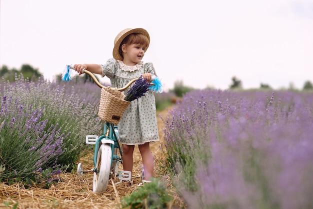 Das mädchen fährt fahrrad und fährt auf einem lavendelfeld.