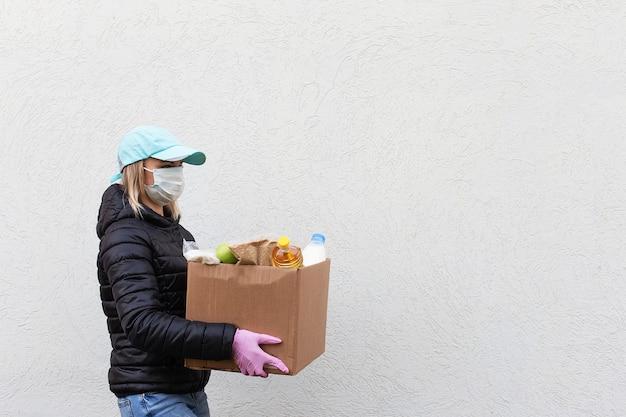 Das mädchen freiwillig in schutzmaske mit lebensmittelbox, spende Premium Fotos