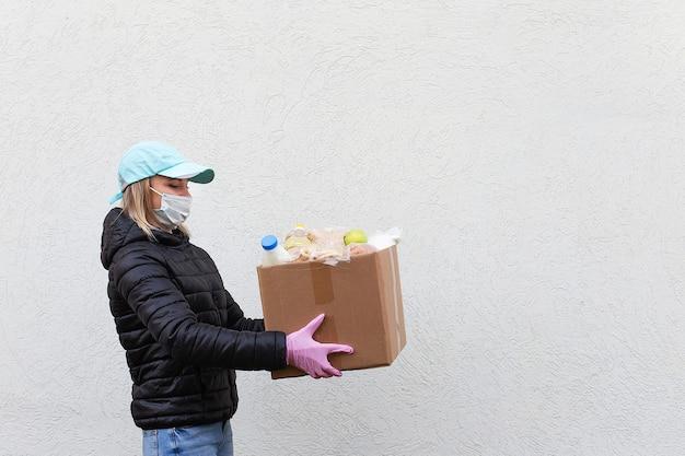Das mädchen freiwillig in schutzmaske mit lebensmittelbox, spende