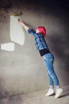 Das mädchen führt reparaturen in der wohnung durch. umzug in eine neue wohnung. der arbeiter macht reparaturen, verputzt und bohrt die wand.