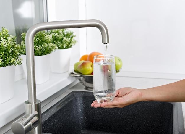 Das mädchen füllt ein glas mit wasser aus einem wasserhahn in der küche.