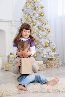 Das mädchen gab ihrem bruder ein geschenk und schließt die augen