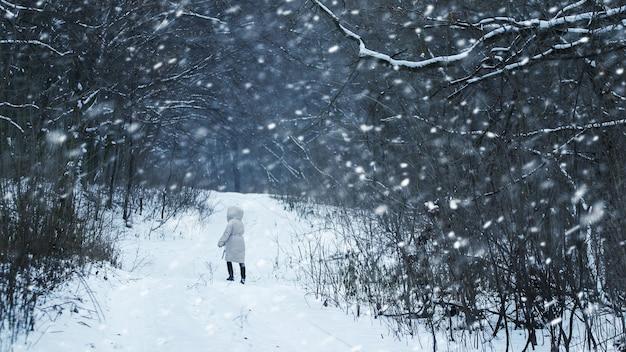 Das mädchen geht bei starkem schneefall im winterwald spazieren. das mädchen hat sich während eines schneesturms im wald verirrt