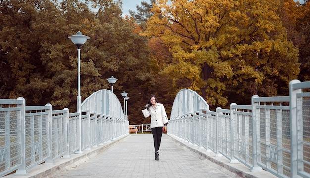 Das mädchen geht die herbstbrücke entlang. junge frau, die auf einer fußgängerbrücke im park geht. brünette in stilvoller herbstkleidung geht im herbstpaar im freien spazieren