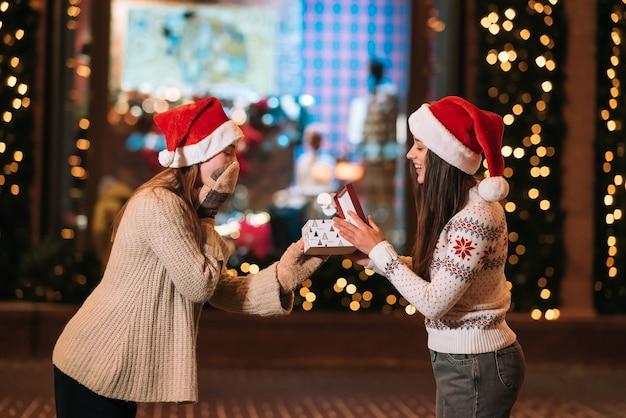 Das mädchen gibt ihrer freundin auf der straße ein geschenk. porträt von glücklichen netten jungen freunden