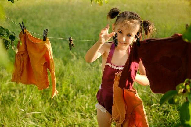 Das mädchen greift mit der hand nach der wäscheklammer, um nach dem waschen kleidung zum trocknen aufzuhängen