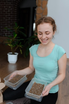Das mädchen hält behälter mit gepflanzten microgreens von rucola und basilikum. hausgartenarbeit