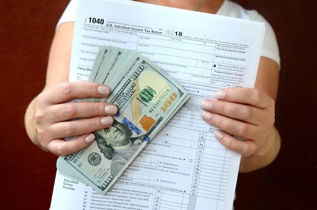 Das mädchen hält das steuerformular und eine große anzahl von dollarnoten in der hand