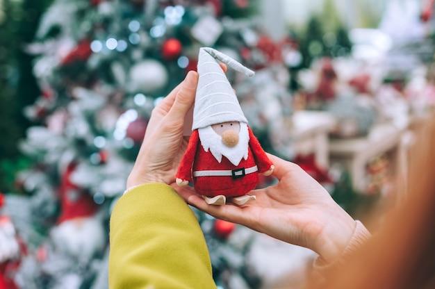 Das mädchen hält den weihnachtsmann - den gnom in den händen
