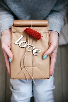 Das mädchen hält ein charmantes geschenk für ihre lieben in den händen
