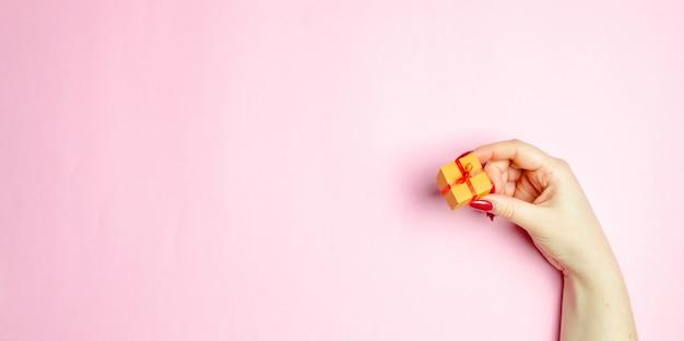 Das mädchen hält ein geschenk auf einem rosa hintergrund aus