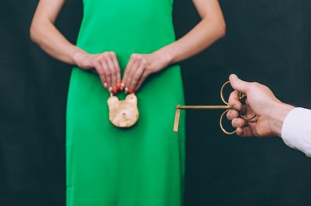 Das mädchen hält ein goldenes türschloss in den händen und der mann öffnet es mit einem schlüssel. symbol des verbots und der treue.