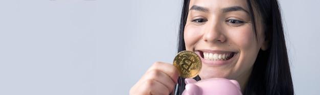 Das mädchen hält ein rosa sparschwein und eine münze in den händen. das konzept von reichtum und akkumulation.