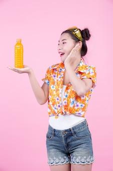 Das mädchen hält eine flasche orangensaft auf einem rosa hintergrund.