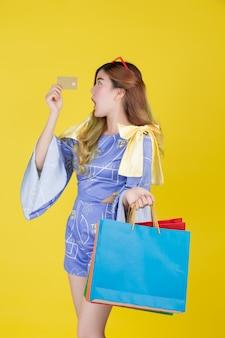 Das mädchen hält eine modeeinkaufstasche und hält eine chipkarte auf einem gelben hintergrund.