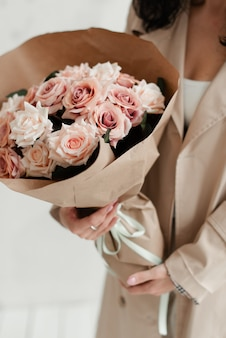 Das mädchen hält einen blumenstrauß in der hand. ein rosenstrauß als geschenk. künstlicher blumenstrauß. dekorativer strauß in papierverpackung.
