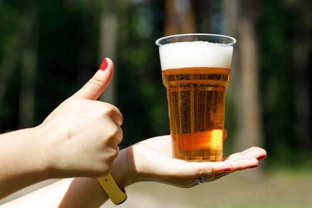 Das mädchen hält einen einweg-plastikbecher mit bier in der hand.