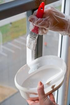 Das mädchen hält einen pinsel mit einem roten stift in der hand und wird das balkongeländer mit weißer farbe streichen