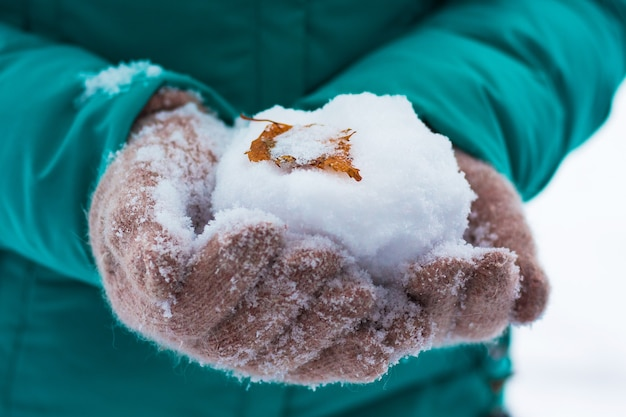 Das mädchen hält einen schneeball in den händen, auf dem das birkenblatt liegt_
