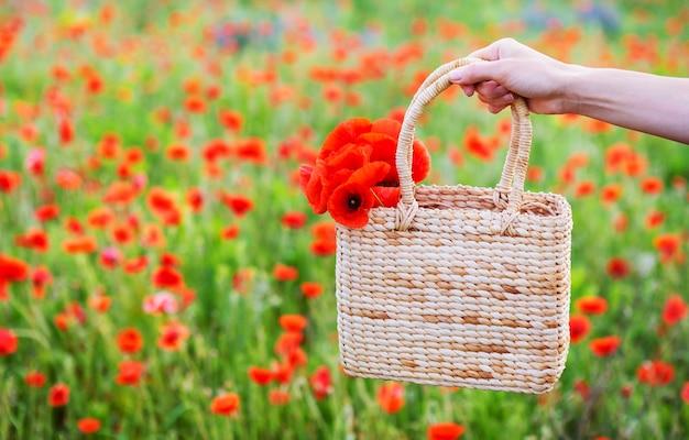 Das mädchen hält einen schönen strauß roter mohnblumen in einem strohsack auf dem hintergrund eines mohnfeldes. nahaufnahme. sommer, erholung im freien.