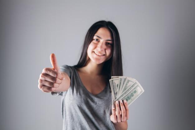 Das mädchen hält geld in den händen und zeigt mit dem daumen nach oben