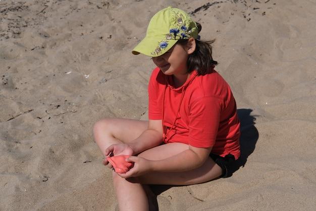 Das mädchen hat roten schleim in den händen. das mädchen ist immer begeistert davon, mit schleim zu spielen, selbst am strand beruhigt sie das spielen mit schleim.