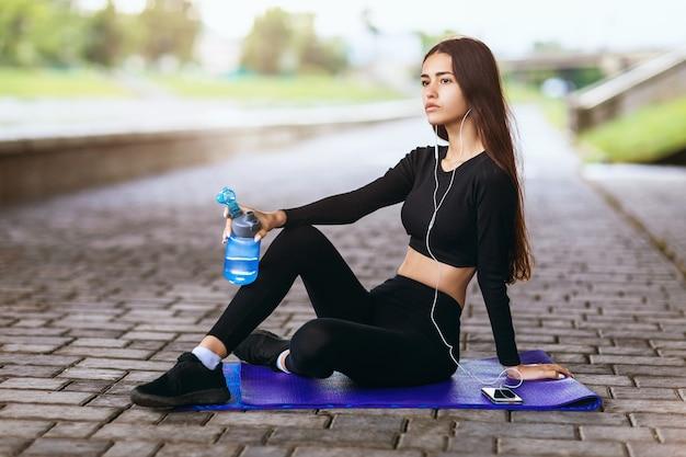 Das mädchen hört musik, während es auf einem gymnastikteppich sitzt, und ruht sich nach dem sport aus