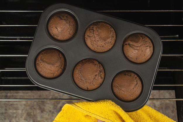 Das mädchen holt ein backblech mit schokoladenmuffins aus dem ofen.