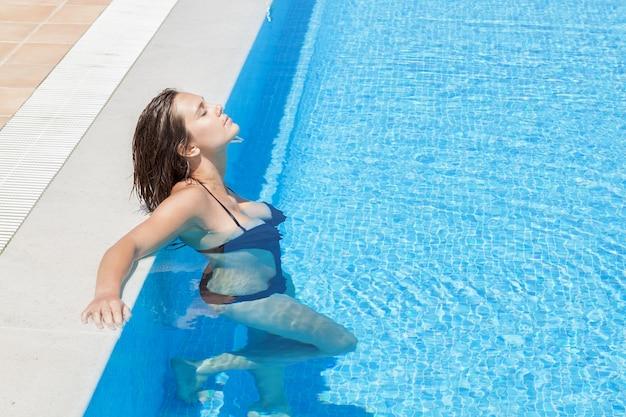 Das mädchen im badeanzug am pool im wasser ruht im urlaub.