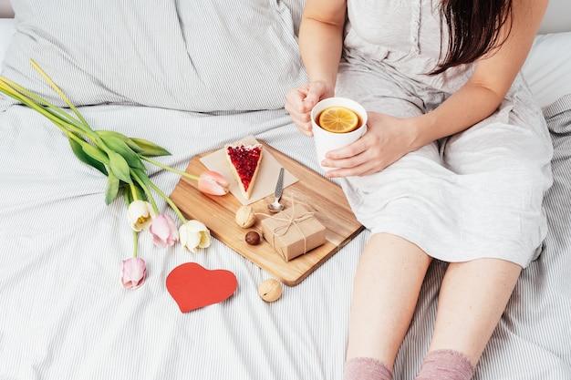 Das mädchen im bett am morgen erhielt blumen, geschenke und frühstück im bett. herzlichen glückwunsch zum valentinstag.
