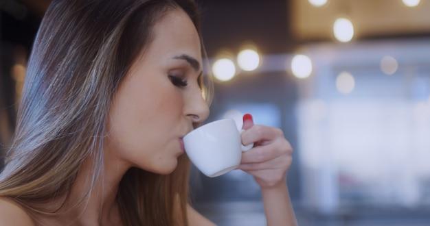Das mädchen im café, eine schöne junge frau in einem café, die den geschmack des getränks genießt.
