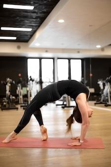 Das mädchen im fitnessstudio macht yoga, um sich in form zu halten oder übergewicht zu kontrollieren.