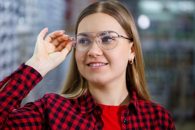 Das mädchen im hemd nimmt eine brille heraus und misst an sich selbst