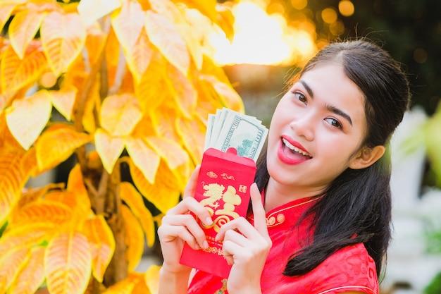 Das mädchen im roten kleid chinesischer abstammung ist mit dem roten umschlag mit dem dollar glücklich.