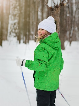 Das mädchen im skianzug verwandelt sich in einen winterwald