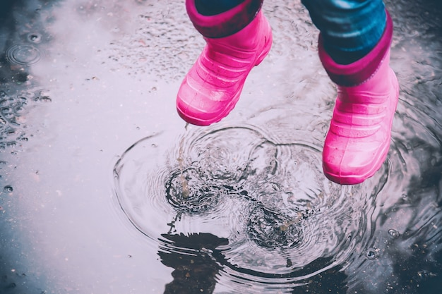 Das mädchen in den rosa stiefeln, die draußen in pfützen nach regen springen.