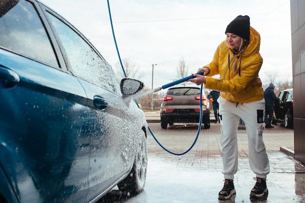 Das mädchen in der autowaschanlage wäscht ihr auto selbst