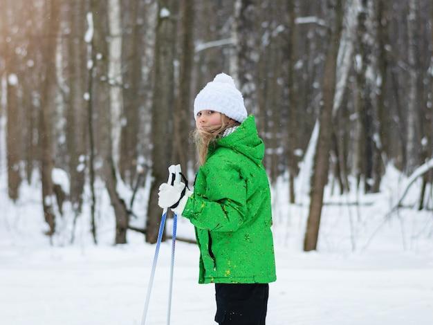 Das mädchen in der grünen jacke in der sonne im winterwald auf skiern