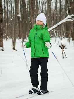 Das mädchen in der grünen jacke und im weißen hut posiert auf skiern im winterwald
