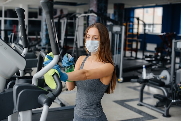 Das mädchen in der maske desinfiziert die fitnessgeräte während einer pandemie.