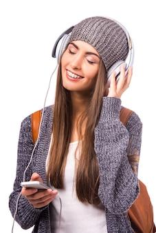 Das mädchen in der mütze lächelt und hört musik.