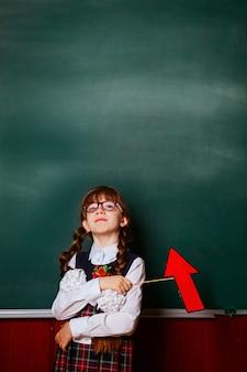 Das mädchen in der schuluniform steht auf einem hintergrund einer kalkhaltigen schulbehörde im klassenzimmer mit einem roten pfeil in den händen.