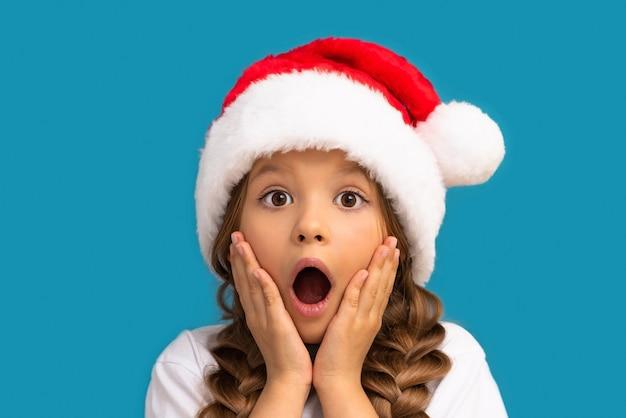 Das mädchen in der weihnachtsmütze ist sehr überrascht.