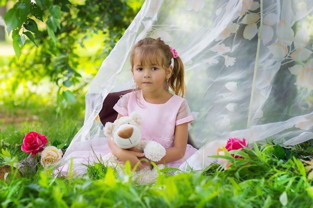 Das mädchen in einem eleganten kleid sitzt mit einem teddybären in einem zelt im freien