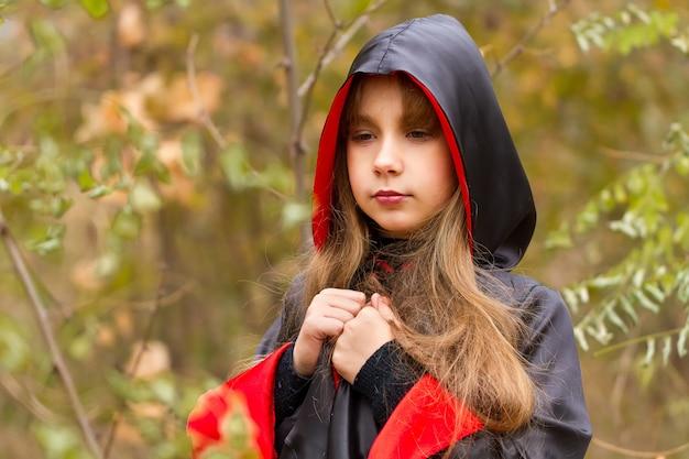 Das mädchen in einem roten und schwarzen umhang im wald